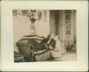 Unidentified man reclining on sofa with a book, Piazza, Castle Tucker, Wiscasset, Maine, undated