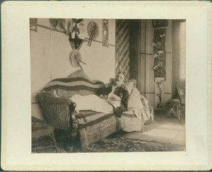 Unidentified man reclining on sofa while reading, Piazza, Castle Tucker, Wiscasset, Maine, undated