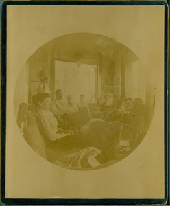 Informal group portrait of the Tucker family seated indoors, unknown location
