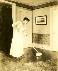 Woman, possibly a domestic, cleaning a floor
