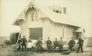 Men leaning against life boat, with dog at their feet, Life Saving Station, Biddeford Pool, Me.