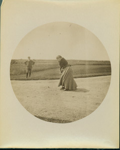 Woman golfer standing in sand trap, in process of swinging club