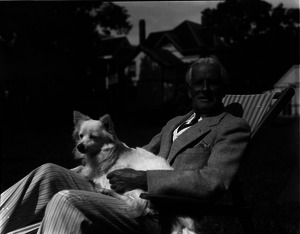 Charles Meyers and dog, reclining on a lawn
