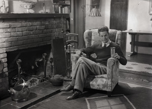 Carl Miller seated by fireplace