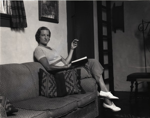Gertrude Kear (?) posed, seated on a couch, smoking