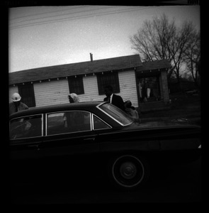 Couple and a car parked in front of a shotgun-style house