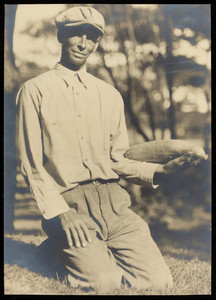 A man kneeling on the grass holding a cucumber or squash.