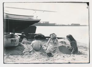 A Woman and Children play in the sand