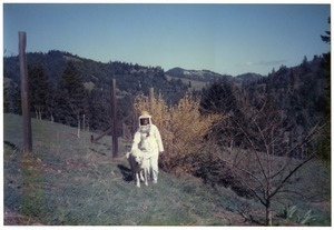 Sandi Sommer in beekeeping suit, with Maya the dog