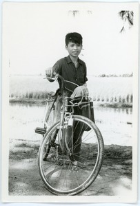 Boy with bicycle in countryside