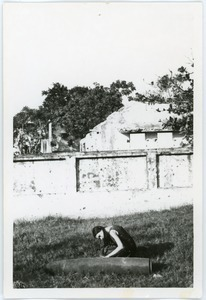 Naomi Jaffe examining unexploded bomb, in front of ruins