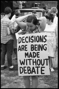Anti-war protester fixing her hair and wearing a sandwich board reading 'Decisions are being made without debate'