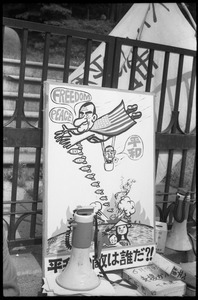 Protest sign depicting President Johnson dangling puppet Japanese prime minister and dropping bombs on Vietnam