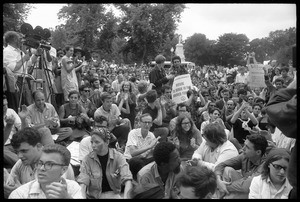 Anti-Vietnam war protesters sitting down after Assembly of Unrepresented People peace march, raising signs 'Refuse to serve in the armed forces'