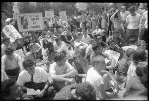 Anti-Vietnam war protesters sitting down after Assembly of Unrepresented People peace march, raising signs 'They need bread not bombs'