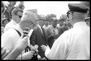 David Dellinger (center) being interviewed by the press after the Assembly of Unrepresented People peace march was attacked with red paint by right wing counterprotesters