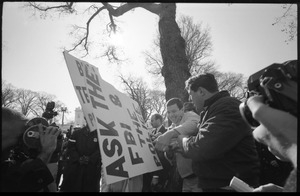 Counter-protesters opposing the antiwar march, struggling over a sign reading 'Ask the FBI and the police', news media looking on: Washington Vietnam March for Peace