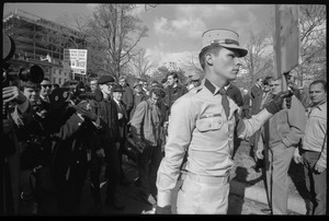 American Nazi Party counter-protester Douglas L. Niles, in uniform, walking away from news media: sign in background reads 'Beatniks, Vietniks, sedition mongers, and all other assorted traitorous cowardly scum, drop dead twice': Washington Vietnam March for Peace