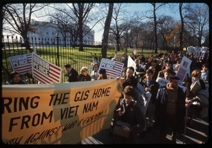Antiwar protesters march past the white house with a banner reading 'Bring the GIs home from Viet Name' and signs reading 'Honor peace': Washington Vietnam March for Peace