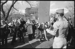 American Nazi Party counter-protester Douglas L. Niles (back to camera), in uniform, carrying a sign, and facing news media: Washington Vietnam March for Peace