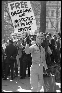American Nazi Party counter-protesterm Douglas L. Niles, in uniform, carrying a sign reading 'Free gasoline and matches for peace creeps': Washington Vietnam March for Peace