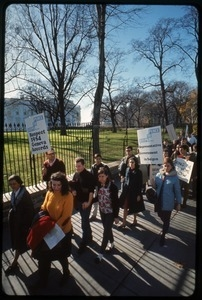 Antiwar protesters march past the white house with signs reading 'Steps to peace... respect 1954 Geneva Accords' and 'Steps to peace... representative government in Saigon': Washington Vietnam March for Peace