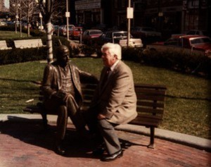 Thomas P. O'Neill seated next to statue of James Michael Curley