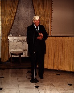 Thomas P. O'Neill speaking at a microphone, pulling at sleeve