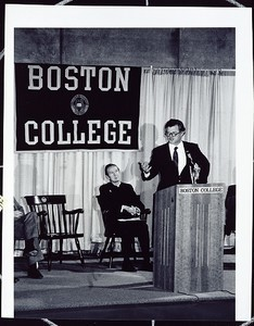 Ted Kennedy speaking at Boston College event, Father Monan in background