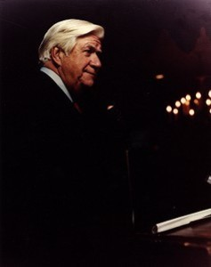 Thomas P. O'Neill speaking at a microphone, dark background