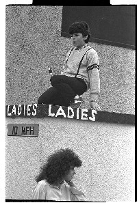 """Young man on roof of """"Ladies'"""" as a woman walks out"""