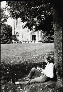 Student reading beneath a tree on the lawn of the Bapst Library at Boston College