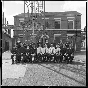 "Andersonstown RUC/PSNI station, West Belfast. Shots taken just before it was demolished. A group of the station's officers pose for the last group photograph within the walls of the compound before vacating the base. Their police station in the background (now demolished) remained hidden behind high security walls for most of the ""Troubles."" Images taken in the years immediately following the change from RUC to PSNI."