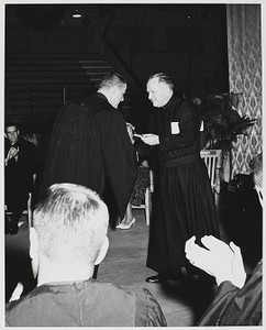 Class Night - Fr. Michael P. Walsh, S. J. gives Peter White his gold medal for General Excellence in the Arts and Sciences and the Cardinal O'Connell Theology Award. Seated in the left hand background is the president of the senior class, Chuck Sullivan