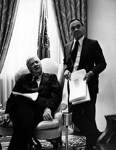 Thomas P. O'Neill smoking cigar in chair, unidentified man standing nearby