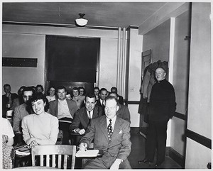 View of Father Ryan with students in classroom at Boston Evening College