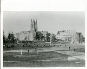 Alumni Field during football practice with view of Devlin Hall under construction and Gasson Hall