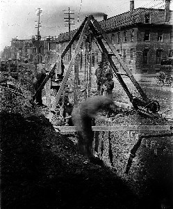 View of workers at construction site at corner of Plympton Street; South End