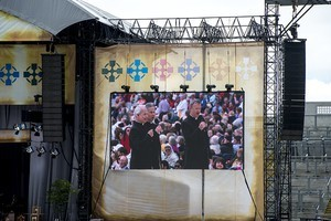 The altar on the large stage, with screens at either side showing 'The Priests' (three priests from Northern Ireland) singing, at the 2012 50th Eucharistic Congress, Final Day Ceremony, 17th June, at Croke Park GAA Stadium, Dublin