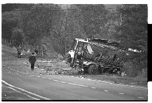 Ballygawley, Co. Tyrone bus bomb scene in which eight British soldiers were killed. Shots of mangled bus, crater where bomb exploded, helicopter and groups of soldiers near the site