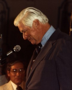 Side shot of Thomas P. O'Neill speaking at a microphone with head bowed