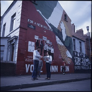 Gerry Adams, President of Sinn Fein, posing in front of a Sinn Fein republican wall mural on the Falls Road, Belfast, and with Mairead Corrigan of the Peace People in front of the mural