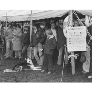 Observers stand under a tent at the Homecoming parade, including a husky