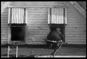 Fire fighter crawling into the second floor of a house on fire