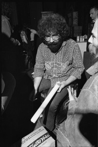 Grateful Dead performing at the Music Hall: Jerry Garcia backstage holding a rolled-up poster and cigarette