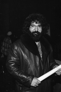 Grateful Dead performing at the Music Hall: Jerry Garcia backstage in a leather jacket and holding a rolled-up poster