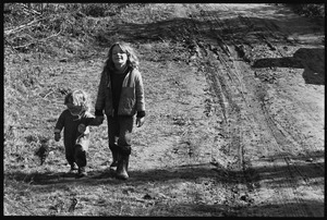 Young girl leading a toddler by hand down a muddy road, Earth People's Park