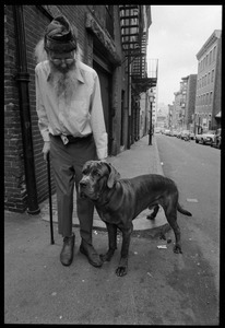 Prescott Townsend standing with a large dog on a Beacon Hill street