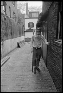 Prescott Townsend walking with a cane up a Beacon Hill alley