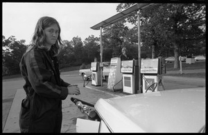 Young woman in overalls, pumping gas at an Exxon service station